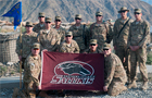 Soldiers in Afghanistan hold up a Saluki flag