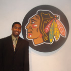 Greg Gilleylen stands by the Chicago Blackhawks logo